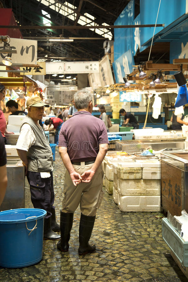 Men talking in fish market royalty free stock photo