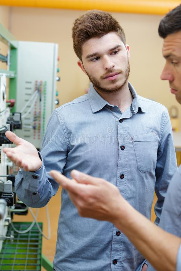 Men talking next to control panel royalty free stock photos