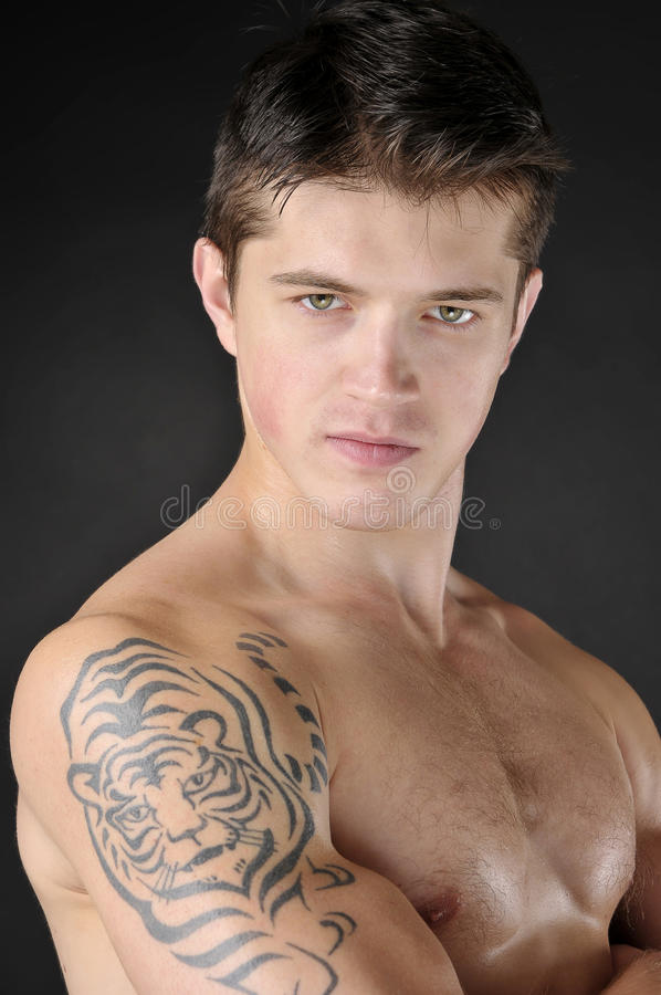 Men with tattoo of tiger on shoulder. Portrait of attractive man with tattoo of tiger on shoulder royalty free stock photos
