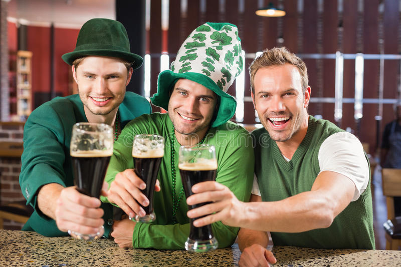 Men toasting with beers. In a bar royalty free stock photo