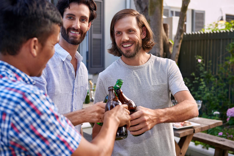 Men toasting with beers. Young men cheers toasting alcoholic beer bottles at outdoor garden party royalty free stock image