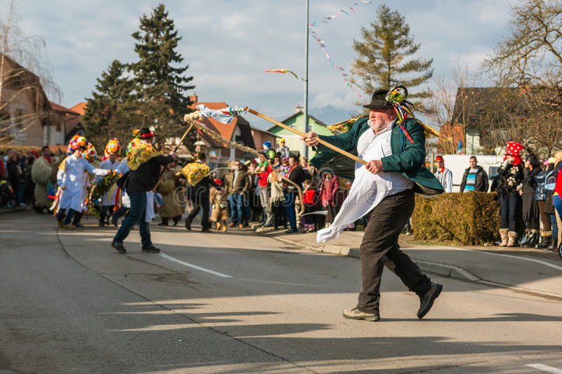 Men in traditional costumes wielding a whip. VIR, SLOVENIA - FEBRUARY 15 2015: Men in traditional costumes wielding a whip on the `Striček` parade on the stock photo