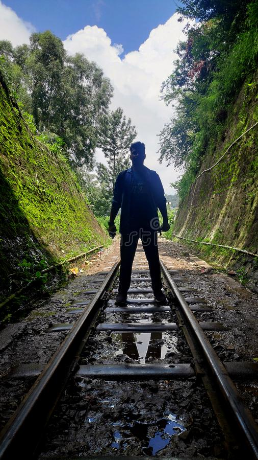 Men in train tunnel of India. Standing furiously  on the track stock image