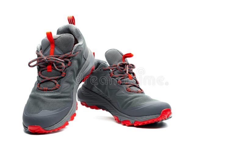 Men trekking shoes isolated on white background. Gray-red hiking shoes. Safety footwear for climbing. Adventure gear. Lightweight stock photo