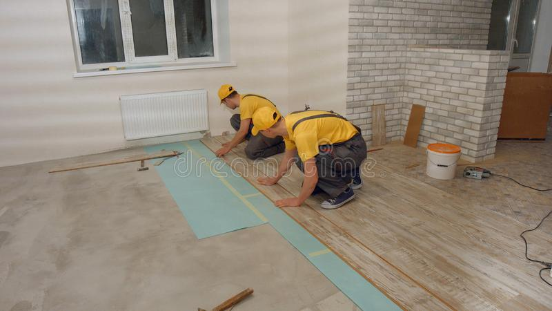 Men in the uniform laying laminate. stock photos