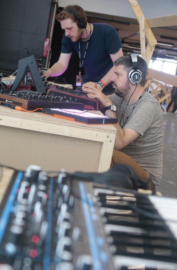 Men using music synthesizer mixing system at sonar festival vertical. Musicians play and test mixing and composing sound systems during Sonar advanced technology stock image