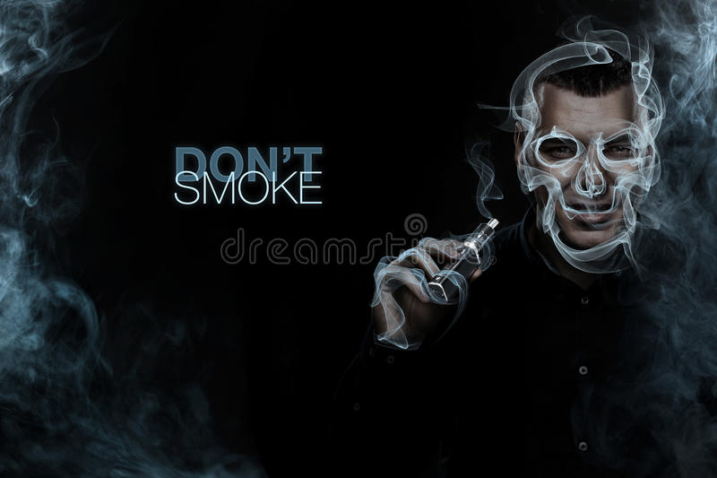 Men vaping and releases a vapor cloud in the form of skull. Social advertisement concept royalty free stock photography