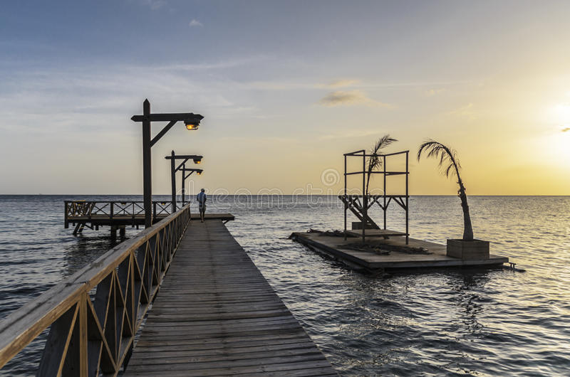 Men waking in a long wooden fishing pier at sunset royalty free stock image