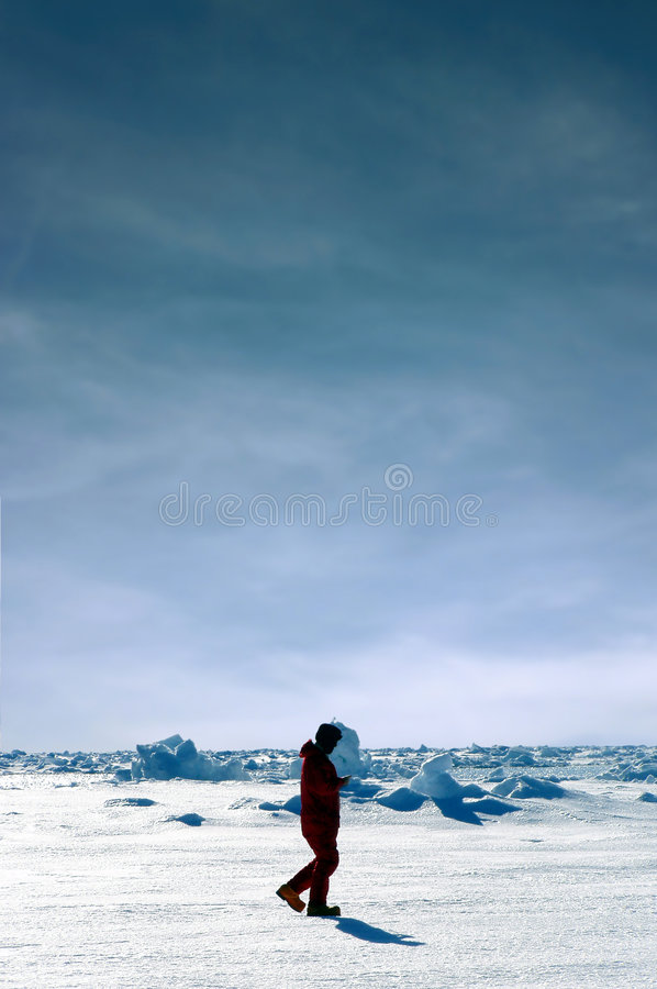 Men walking in Antarctica. A silhouette of a man walking in Antarctica. he's surrounded by white snow and ice. There is a cloudy sky stock photos