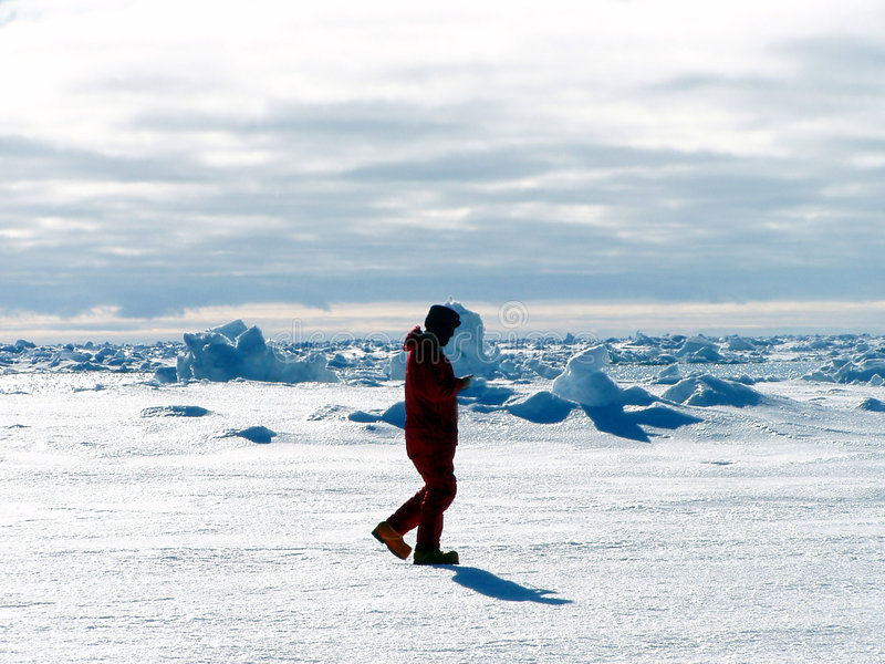 Men walking in Antarctica. A silhouette of a man walking in Antarctica. he's surrounded by white snow and ice. There is a cloudy sky stock image