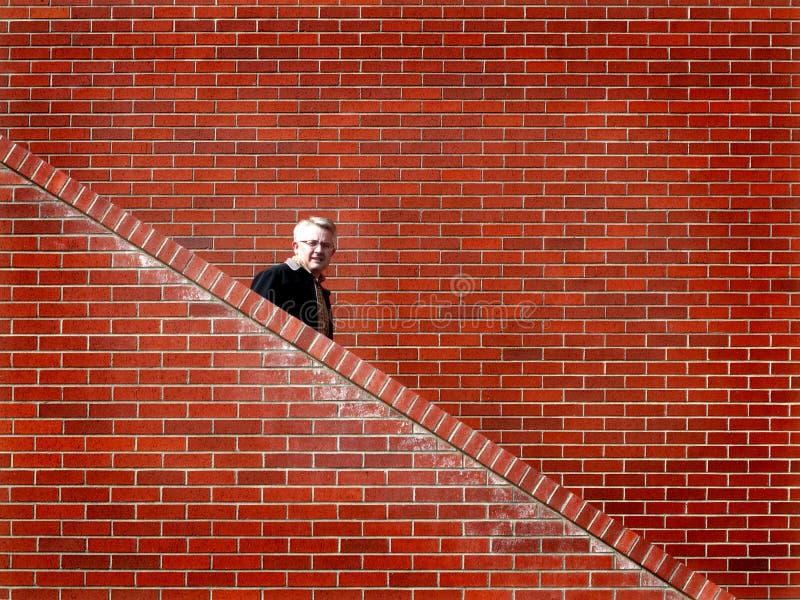Men Walking down Stairs Brick Wall. Man walking down stairs with brick wall in background stock photos