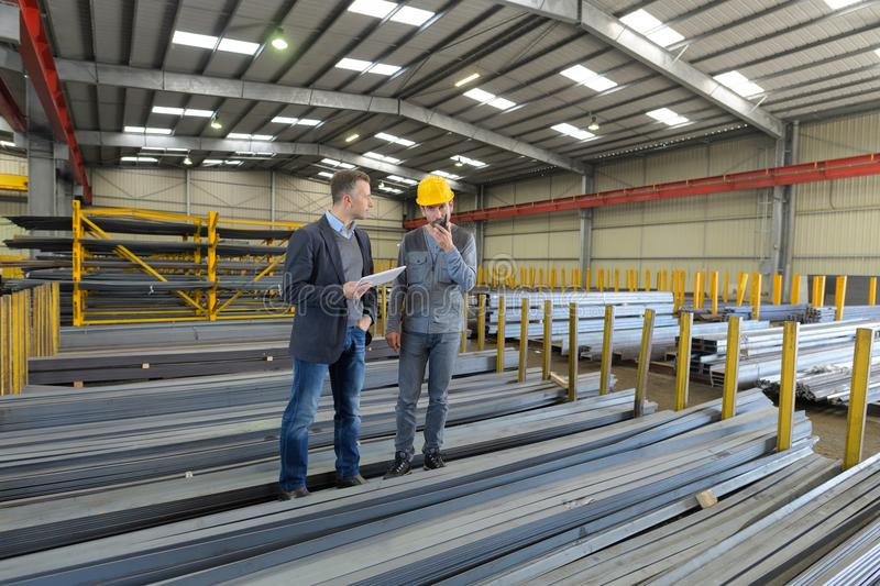 Men in warehouse metal lengths one on walkie talkie. Men in warehouse of metal lengths one on walkie talkie royalty free stock photos