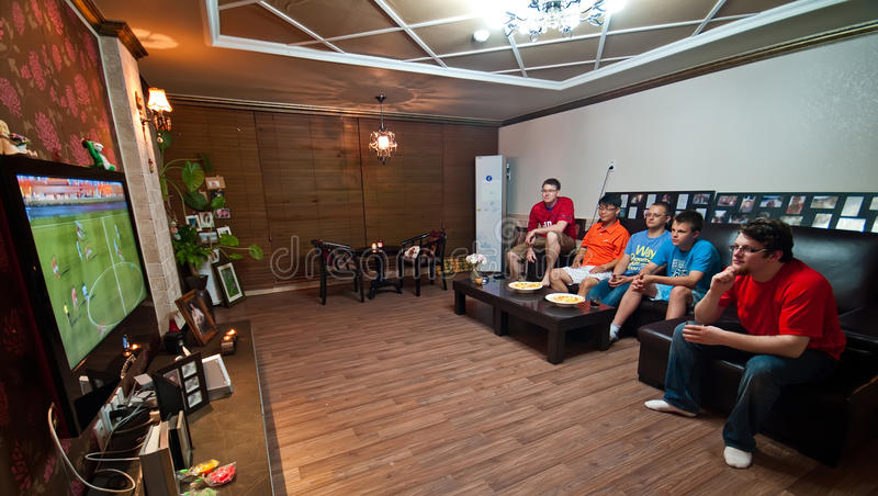 Men watching football on TV. Group of men with boy watching football match on television indoors stock images