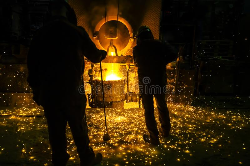 Men watching sparkling melting steel in furnace of foundry. stock photography