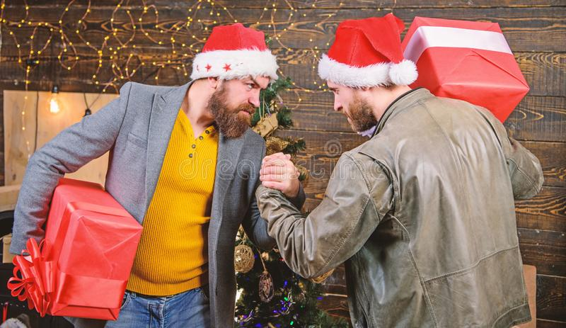 Men wear santa hat hold gift boxes. Bearded men carry present boxes. Brutal hipster guys celebrate christmas with gifts royalty free stock photo