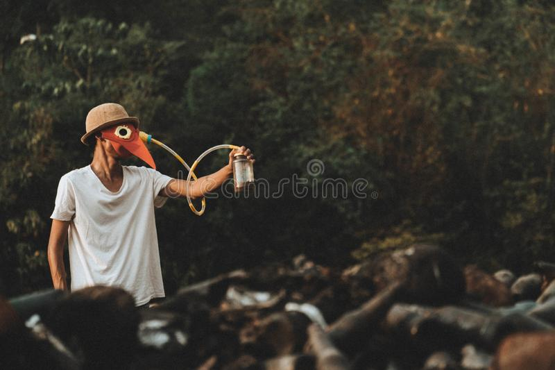 Men wear a toxic mask with a long cord attached to a glass bottle with trees growing inside a glass bottle to create oxygen.concep. T for save the world and royalty free stock photo