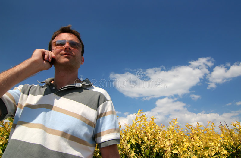 Men whit phone. Men phone at yellow bush and blue sky royalty free stock photography