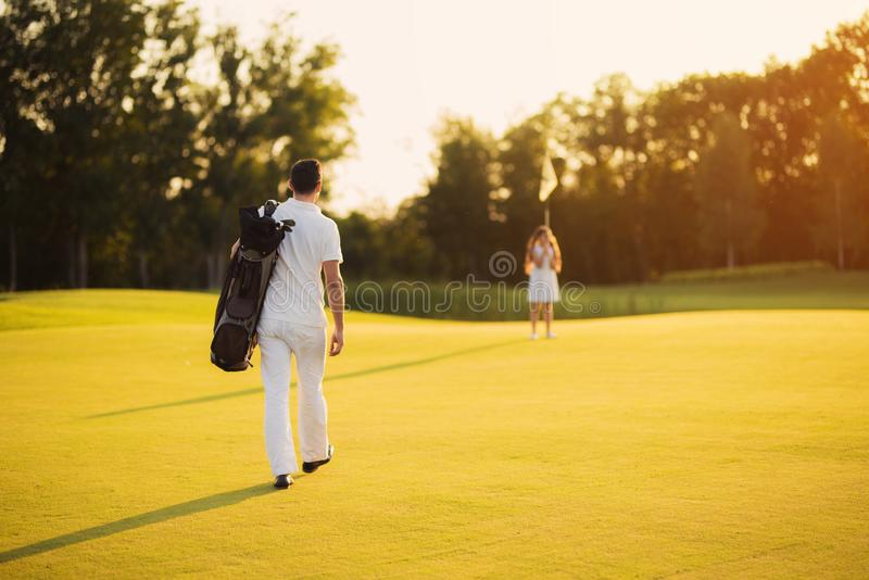 A man walks along the golf course with a golf club bag and heads towards the girl who is standing in front of him royalty free stock photo