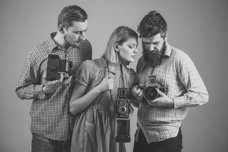 Men, woman on concentrated faces looks at camera, grey background. Company of busy photographers with old cameras. Men, women on concentrated faces looks at stock photo