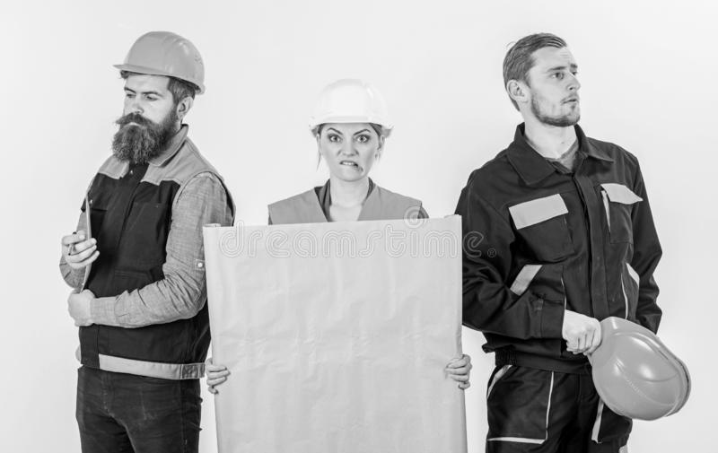 Men and woman in helmets, architects on confused expression. Men and women in helmets, architects on confused expression with drawing, plan, blueprint, project royalty free stock photography