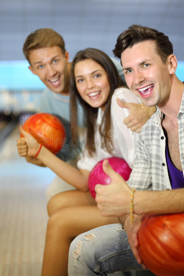 Men And Woman Hold Balls, Thumb Up In Bowling Club Stock Image