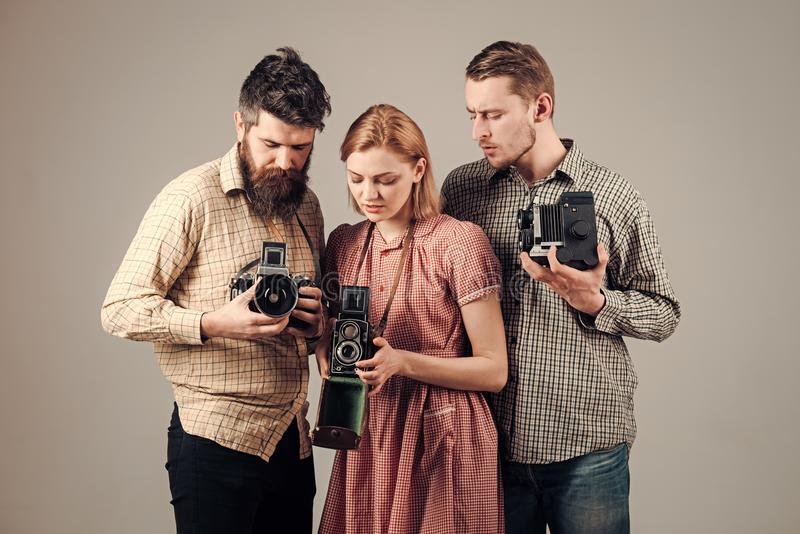 Men, woman on interested faces looks at camera on grey background. Company of busy photographers with old cameras. Men, women on interested faces looks at camera stock photo