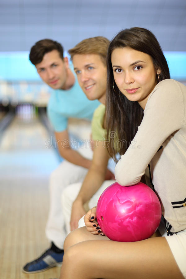 Men and woman sit in bowling club stock images
