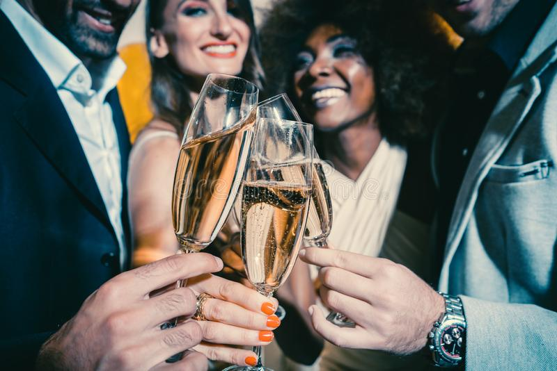 Men and women celebrating party while clinking glasses with sparkling wine stock images