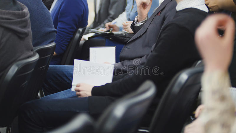 Men and women at a conference or presentation, workshop, master class - pens and notebooks in hand, close up royalty free stock image