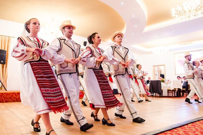 Men and women dancers performing Romanian folk dances stock images