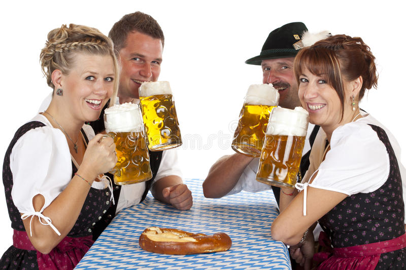 Men and women drinking Oktoberfest beer. Happy Bavarian men and women drink Oktoberfest beer stein. Isolated on white background stock photography