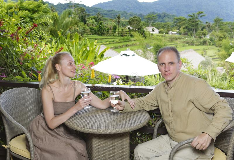 Man and the woman with glasses sit on a balcony overlooking rice terraces and mountains. stock image
