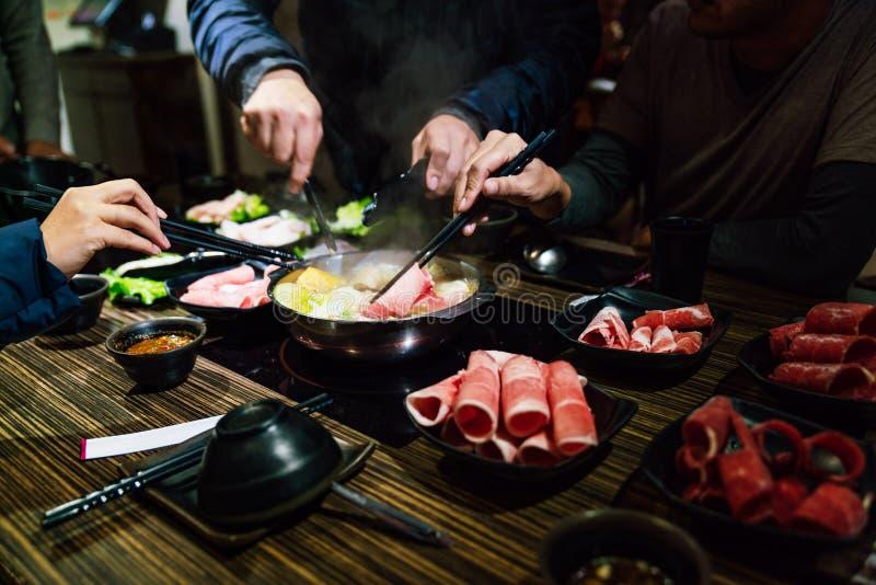 Men and women hands pinching medium rare slice Wagyu A5 beef and Kurobuta pork in hot pot shabu clear soup base by chopsticks. stock photos
