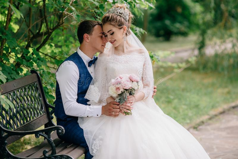 A man and a woman just married they are sitting on a bench in a green quiet park. The bride on the groom`s lap gently stock image