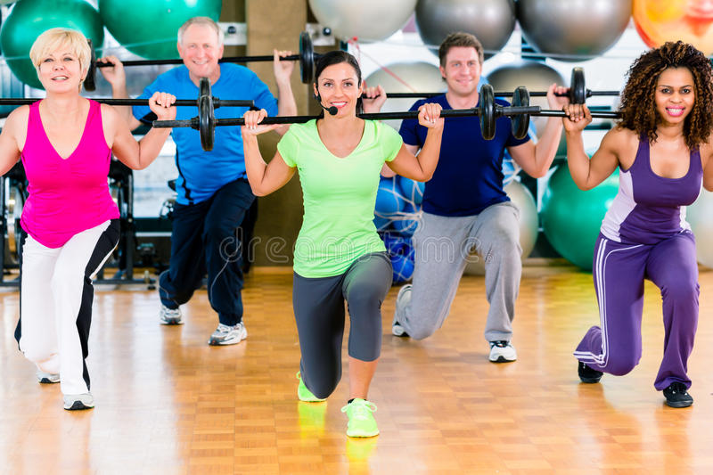 Men and women lifting barbell in gym stock photos