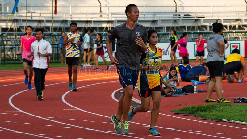 Men and women running on a race track. The athletes practicing on the race track in Chiang Rai stadium. Chiang Rai, Thailand – November 20, 2018 stock image