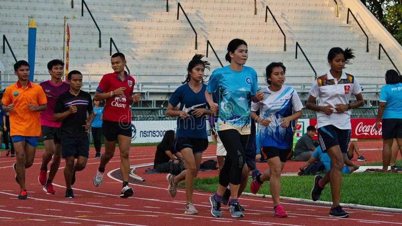 Men and women running on a race track. The athletes practicing on the race track in Chiang Rai stadium. Chiang Rai, Thailand – November 20, 2018 stock photo