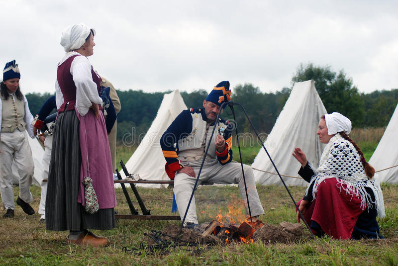 Men and women sit by fire at Borodino battle historical reenactment in Russia. BORODINO, MOSCOW REGION - SEPTEMBER 04, 2016: Men and weman sit by fire at royalty free stock photography