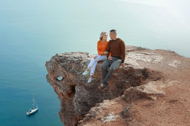 A man and a woman sit on a rock dangling their legs over cliffs royalty free stock photo