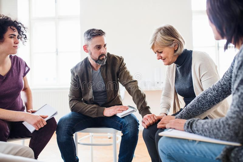 Men and women sitting in a circle during group therapy, supporting each other. royalty free stock photos