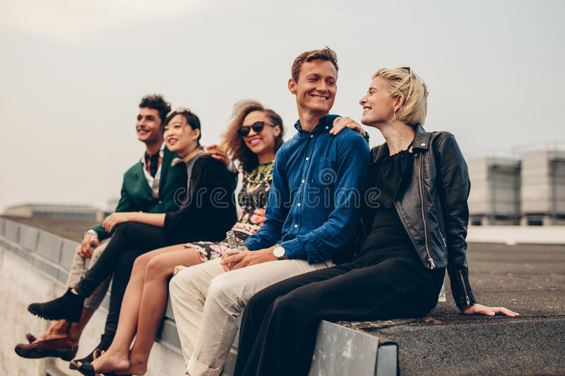 Men and women sitting together on rooftop. Shot of young men and women sitting together on rooftop. Mixed race friends relaxing on terrace royalty free stock photos