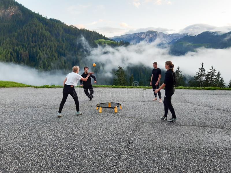 Men and women in their twenties playing a game of spike ball in a mountain parking lot in the Dolomites. Four men and women in their twenties playing a game of stock photography