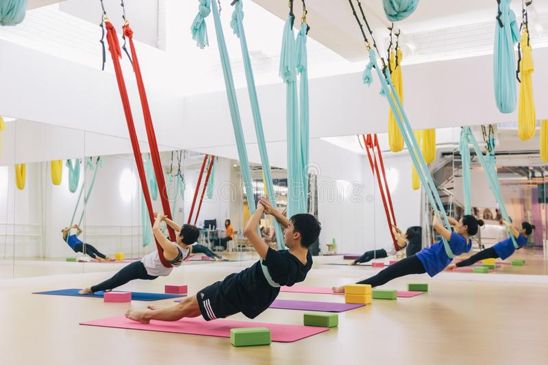 Men and women training yoga by hammocks for Anti-gravity air flying yoga. Wellness for man and woman lifestyle at yoga studio. Men and women training yoga by stock images