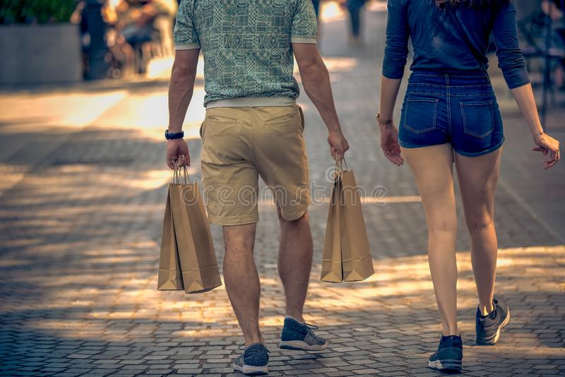 Men and women walk down the street with shopping bags. A beautiful sunny day in the shopping center of the old town center stock photo