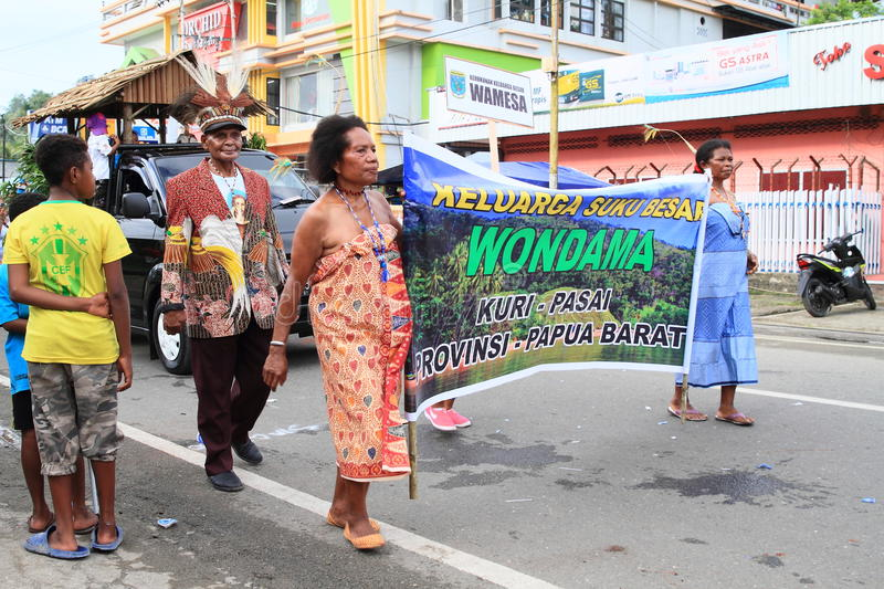 Men and women from Wondama - Papua Barat. Men and women dressed in traditional clothes from Wondama - Papua Barat with sign in procession in occasion of stock photography