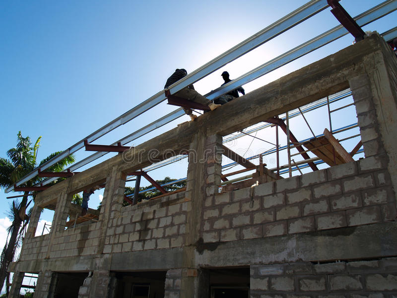 Men at work constructing roof on a concrete building stock image