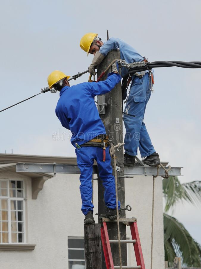 Men at work on electricity column royalty free stock photos