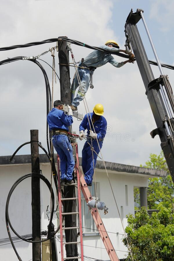Men at work on electricity column stock images