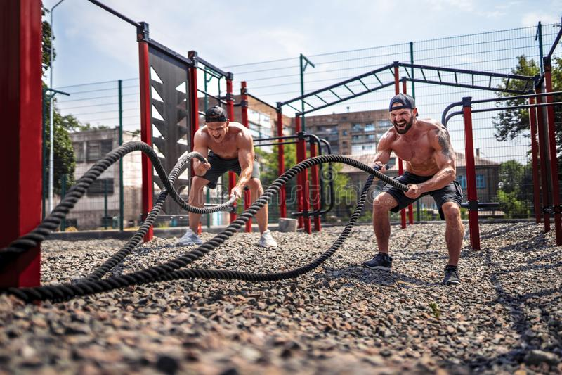 Men work hard with rope at street gym yard. Strength and motivation. Outdoor workout. fitness, sport, exercising royalty free stock photos