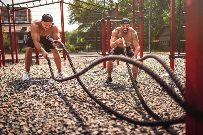 Men work hard with rope at street gym yard. Strength and motivation. Outdoor workout. fitness, sport, exercising stock photo